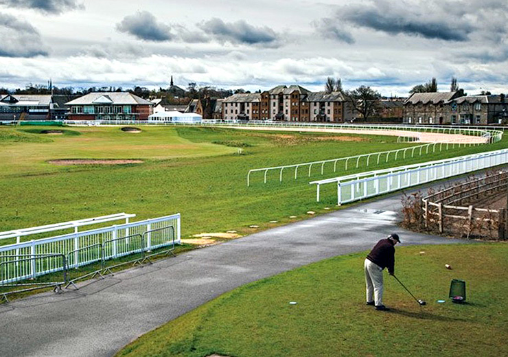 A golfer hits his drive over the horseracing track on the sixth tee box at Musselburgh Golf Links. Photo: Andrew Hetherington